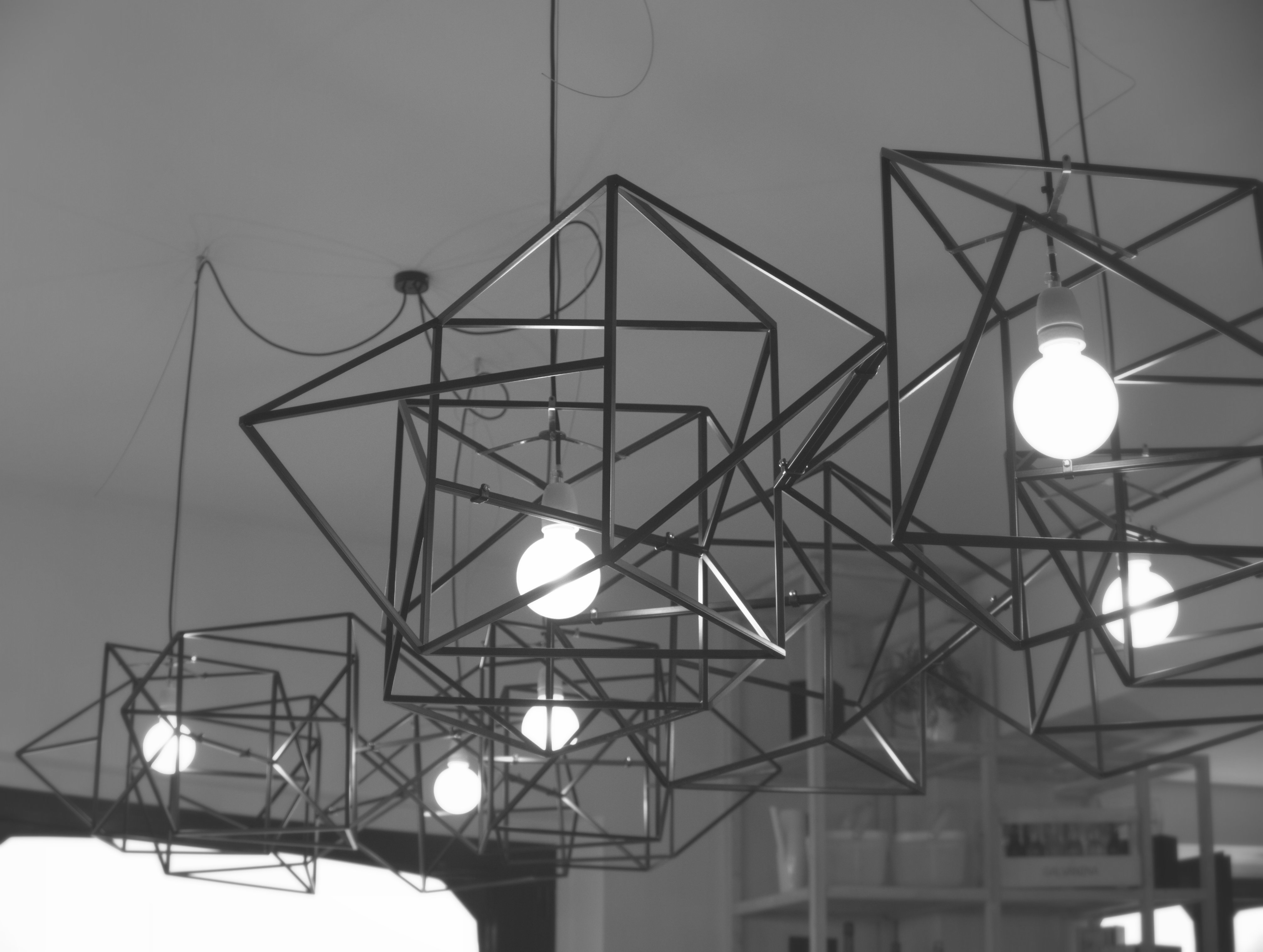 divina proportione lamp black with light on with geometrical forms and shadows in a room bar